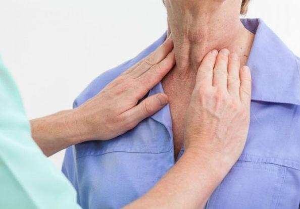 врач ощупывает щитовидку
